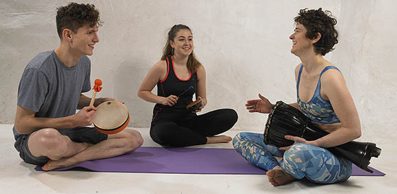 A group of young people drumming and sitting together on a yoga mat. They appear to be having fun