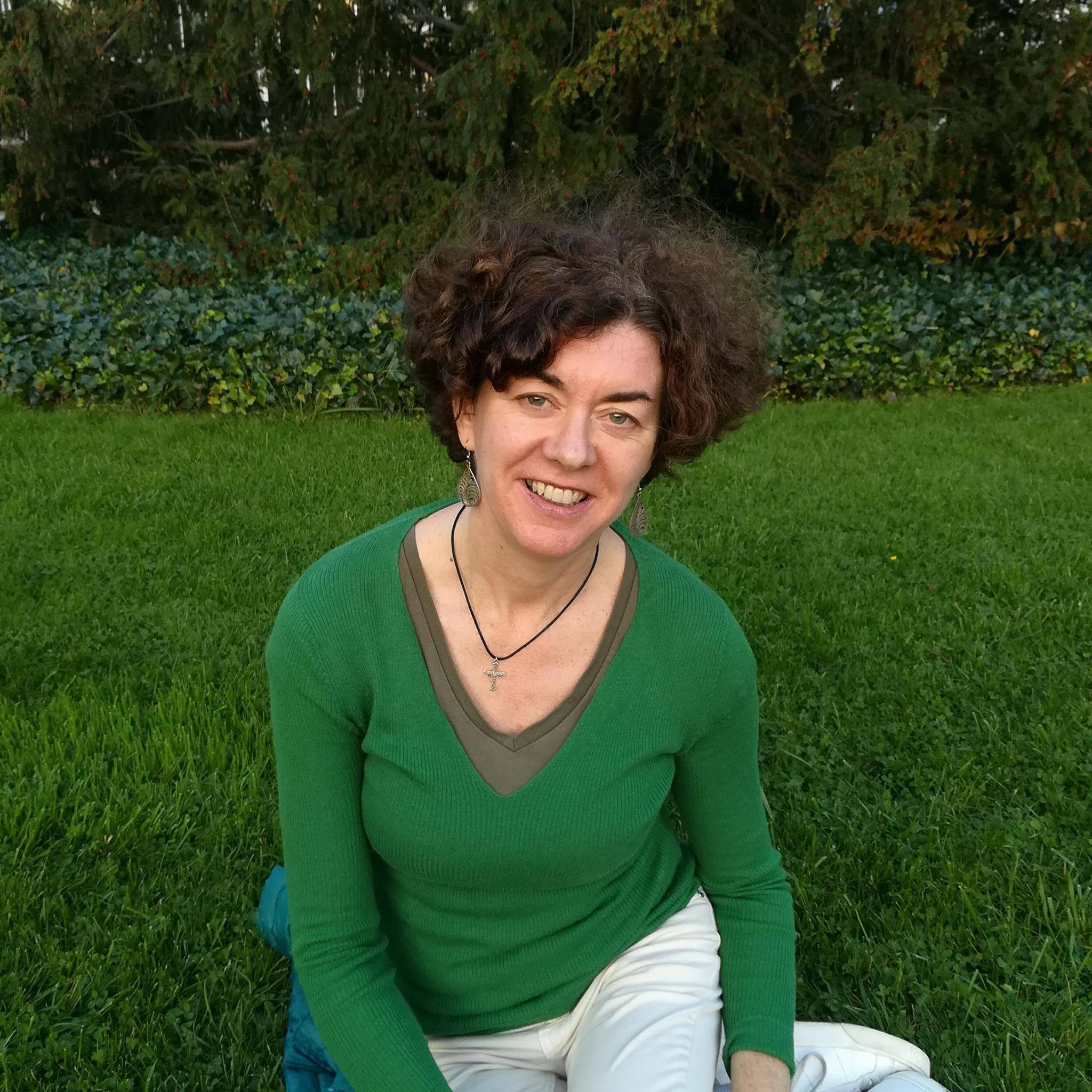 Woman wearing a green shirt against a background of green grass